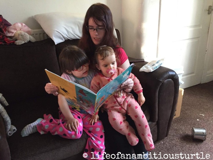 Me sat propped on the sofa, both my daughters on my knee in their fleece pyjamas. I'm reading them their bedtime story.