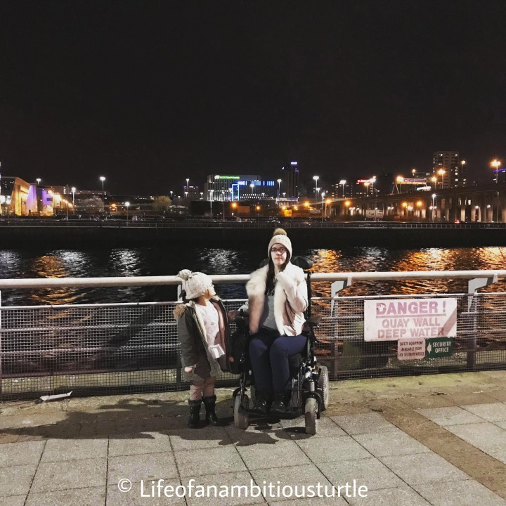Breathtaking image of us infront of the river Clyde. The railing behind us has the twinkling city lights above them