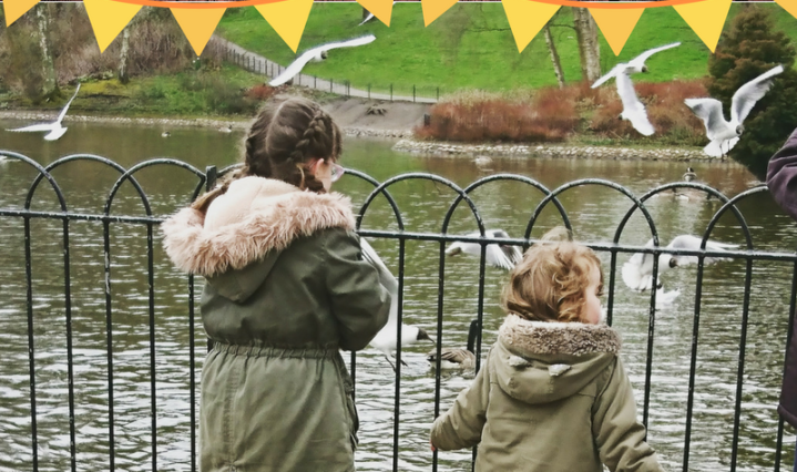 The girls bundled up feeding the ducks at the park