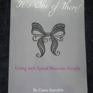 "A photo of Lori's book. The cover is a elegent grey with a frilly black bow outline in the middle, above reads; ""It's One Of Them!"" is cursive. Clicking this image leads to you to Amazon where you can purchase."