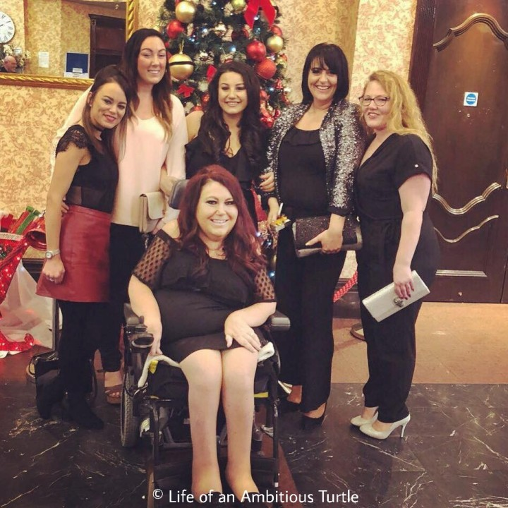 Lori sat in her powerchair wearing a knee length black formal dress, surrounding her are her various long term Personal Assistants with her adult daughter centered behind her. A Christmas tree is visible behind the ground