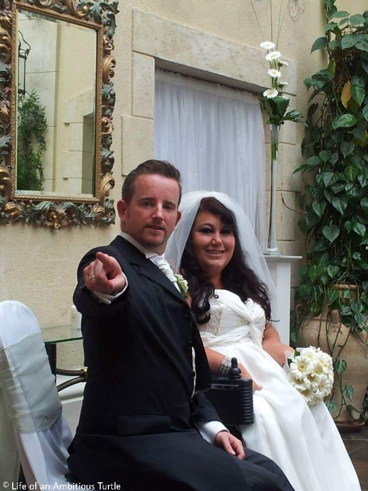 Mike is joking around, sternly pointing at the photographer sat next to a beaming Lori. He is wearing a traditional black tux with white tie and shirt, Lori's dress is white with flowy folds of fabric on the bust, a white vail drapes around her curled hair which she wore down on her special day