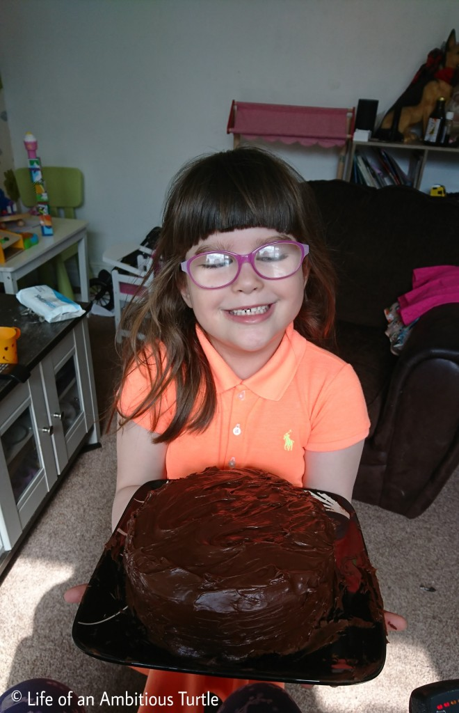 Abbie holding out the chocolate cake for a photo, smiling
