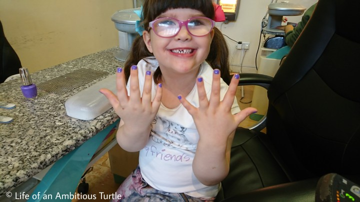 Abbie beaming ear to ear in the Nail Salon showing off her chosen purple polish