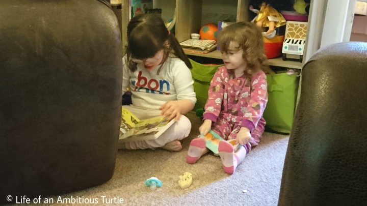The girls sat on the carpet in their pj's reading books together