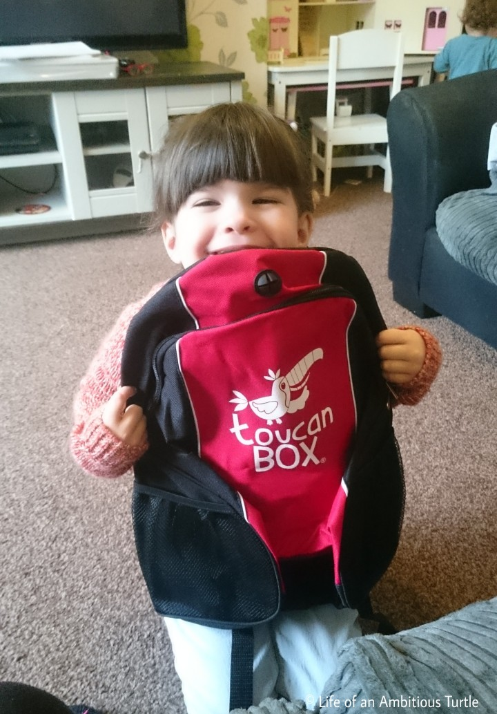 Abbie grinning ear to ear holding her red and black Toucan box backpack out infront of her, the Toucan box logo is clearly visible on the front pocket