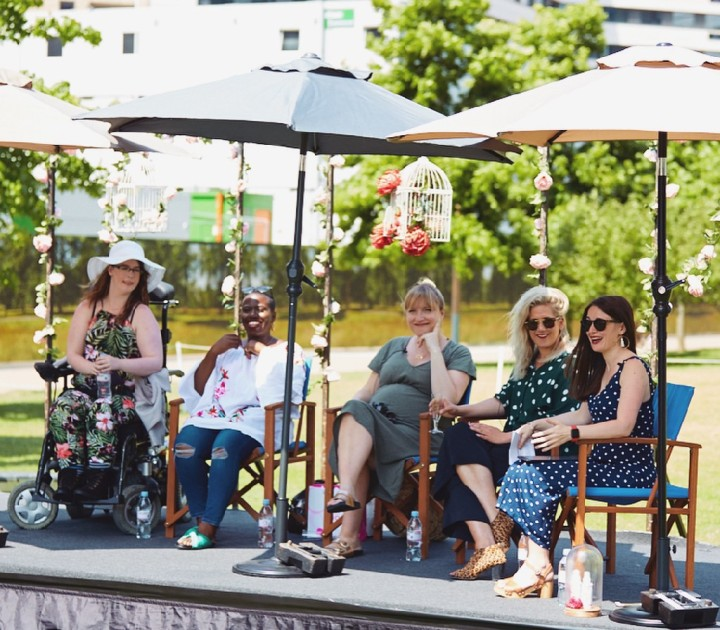 On the panel with other Mummy influencers such as Mother Pukka and NotAnotherMummyBlog. We are all in summer clothing, I'm sporting a sunhat in a playsuit. We're all sat under a canopy in the sunshine with microphones attached