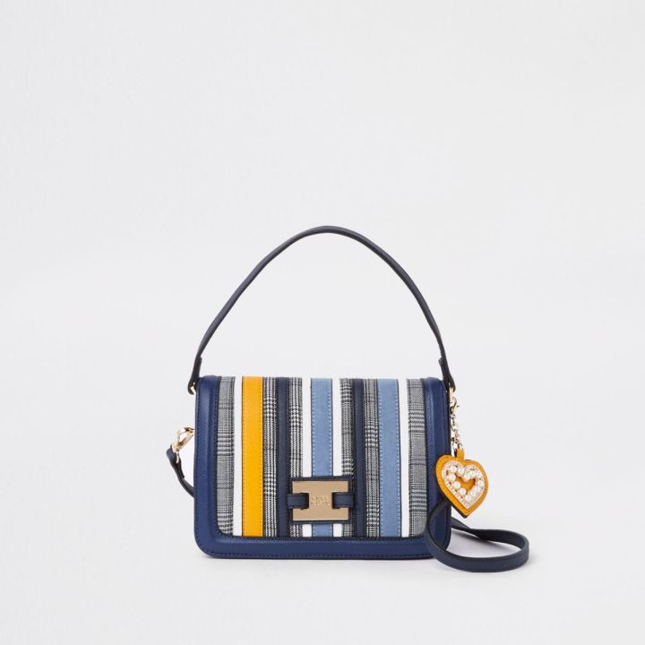 Small-Medium striped cross body leather handbag. Stripes are in navy and pale blue with a few thin white and 1 bold mustard colour stripe. magnetic clasp that flips over itself to fasten. Trademark River Island brand buckle in the lower centre of the flap opening. Comes with leather heart keychain zip pull with glued on pearls in the heart shape