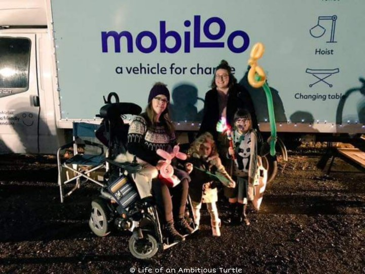 Photo taken with Mobiloo vehicle behind us. It is dark outside and I'm posed in my powerchair with my 2 little girls holding animal balloons and Hannah from Circus Starr all huddled smiling at the camera