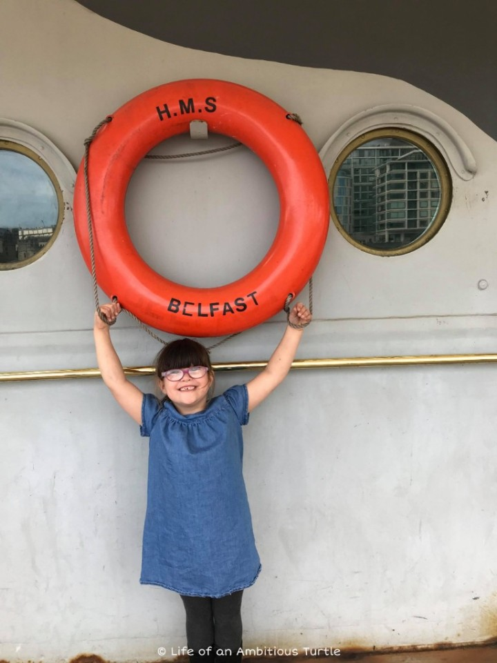 Abbie pretending she's holding up the life saver on the H.M.S Belfast that is attached to the side of the ship
