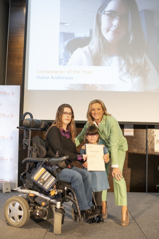 On stage being presented my award by Gabby Logan for Campaigner of the Year 2018. I am sat in my powerchair smiling, my daughter Abbigail is helping hold the award up for photos. Gabby is wearing a light green suit
