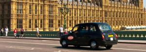 Stock image of a ComCab black cab whizzing past Parliament