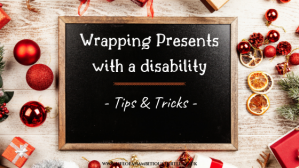 """A blackboard laying flat on a table with scattered red and gold Christmas decorations on it. Upon the board reads; """"Wrapping Presents with a disability - Tips and tricks"""""""