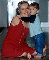 Alison sitting on the floor being hugged around the neck by her toddler son Parys. Both smiling at the camera. Alison has a pixie hairstyle, red lipstick, no arms and only feet attached to her torso as part of her condition