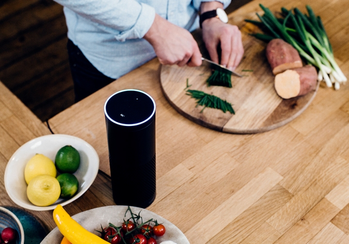 Man chopping vegetables in the kitchen on a wooden cutting board, Amazon Echo next to him talking him through  the cooking method