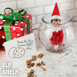 Elf hugging its knees crouched down inside a cookie jar on a kitchen worktop, a little note is placed next to it which reads;