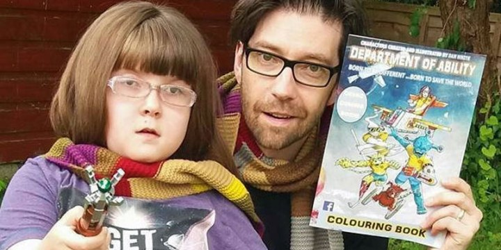 Dan and his daughter Emily, they're wearing Gryffindor scarves from Harry Potter and Dan is holding up a colouring book version of his comic