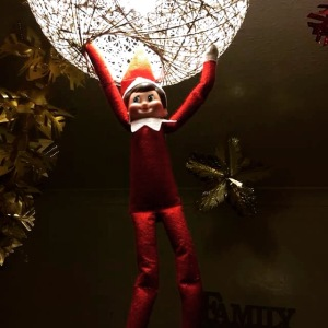 Elf on the Shelf hanging from our wicker light shade