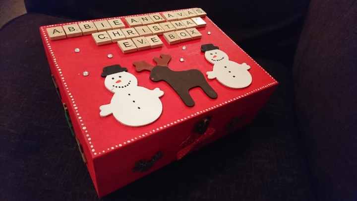 Red painted wooden box with wooden snowmen and reindeer. The girls names are spelt in scrabble letters ontop