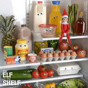 Elf on the shelf sitting inside the fridge on a shelf surrounded by food