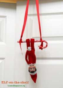 Traditional red elf on the shelf swinging upside down on a candy cane swing attached to ribbon hanging off the top of a door frame
