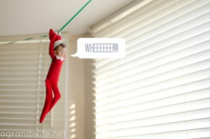 Elf on the shelf ziplining on a string across the ceiling