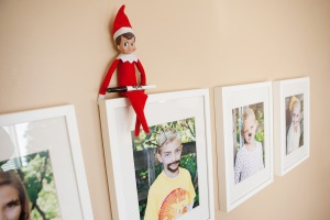 Elf on the shelf sitting proudly onto of a wall mounted family photo frame with a sharpie in hand, elf has appeared to have added beards, cats ears and muchtashes on family members
