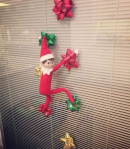 Elf in climbing position on the wall, present bows are used on it's hands and feet to keep it stuck to the wall