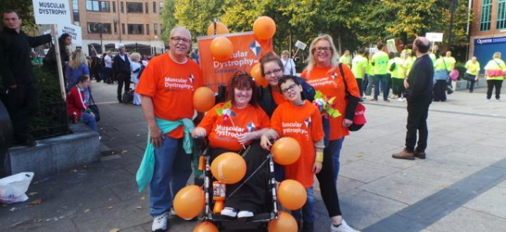 Michaela smiling centre in a huddle of MDUK fundraisers all sporting MDUK orange charity t-shirts after a fun run. Michaela is smiling sat in her powered wheelchair and has deep red shoulder length hair. They all are holding orange charity balloons for the occasion