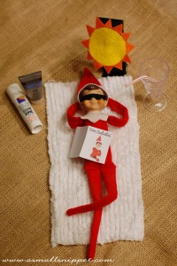 Elf on the shelf appearing to be sun bathing on a bit of cloth, paper book on his stomach, sunnies and cut out sunshine. A pretend glass and straw sits beside him