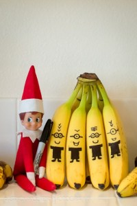 A bunch of bananas with black pen bodies and eyes with glasses on to look like Minions, the elf on the shelf is sat next to the bunch holding a sharpy caught red handed!
