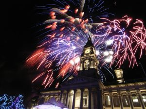 Pink and purple fireworks above the town hall clock