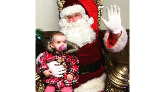 Ava age 1 wearing a red tartan coat, dummy in her mouth sitting on Santa's lap at Santa's Grotto. Santa is waving at the camera