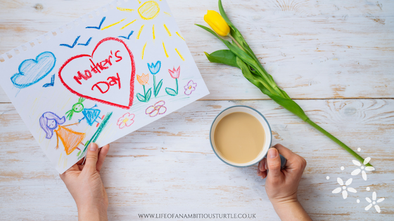 "Image of a Mother's hands, 1 cupping a mug of tea and the other holding a child's drawing of their family with the words ""Mothers Day"" in a big heart."