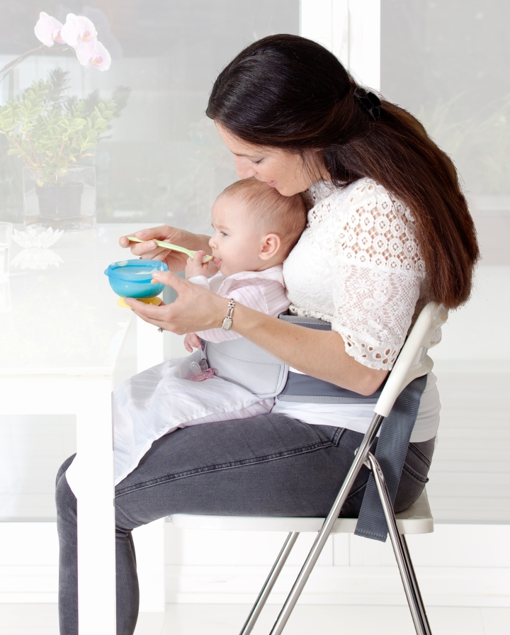 Lady sat at the dining table, baby strapped around her waist with the lapbaby product