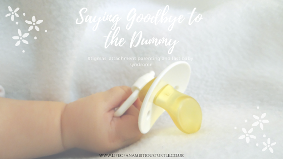 Image of a babys outstretched hand clutching a white dummy
