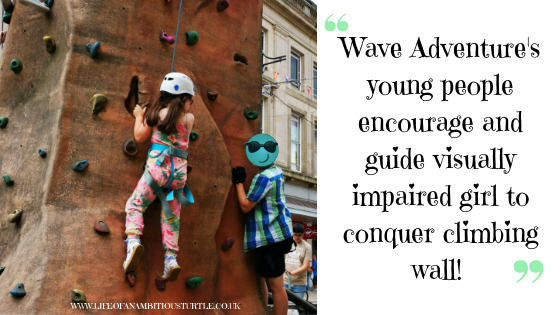 Photo of my eldest daughter Abbie (age 6) wearing peach floral jumpsuit, climbing outdoor climbing wall wearing safety helmet and harness. Her legs are dangling but she's pulling up using her hands in the holes. A 12 year old boy in a blue checked shirt is climbing up the wall beside her offering words of encouragement. Next to the photo it reads;