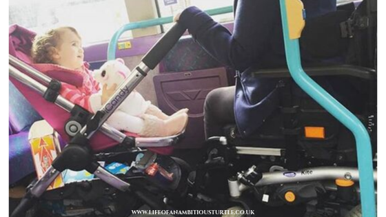 Photo of myself, a powered wheelchair user parked in the wheelchair space on a public bus, infront of me is my youngest daughter smiling in her buggy. We both fit in the single space.