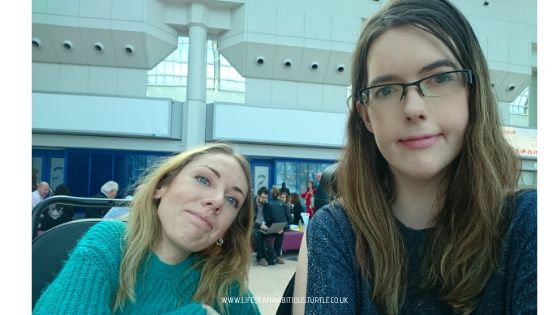 Disability blogger Carrie Aimes, with shoulder length blonde hair and a wooley green jumper and Fi Anderson, swearing an open shoulder navy glittery jumper with shoulder length brunette hair and glasses, sitting side by side having lunch at the Naidex exhibit in NEC Birmingham