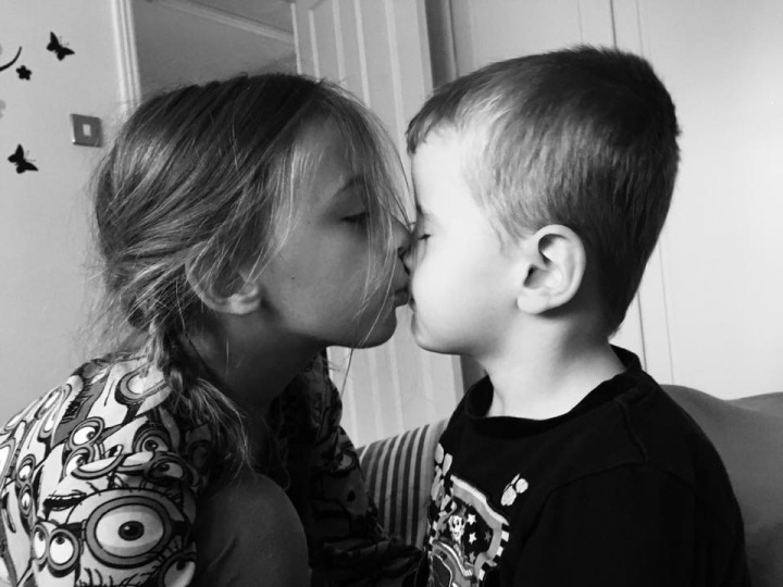 Siblings April (9) and Fraser (5) in a loving black and white photo giving one and other a kiss,