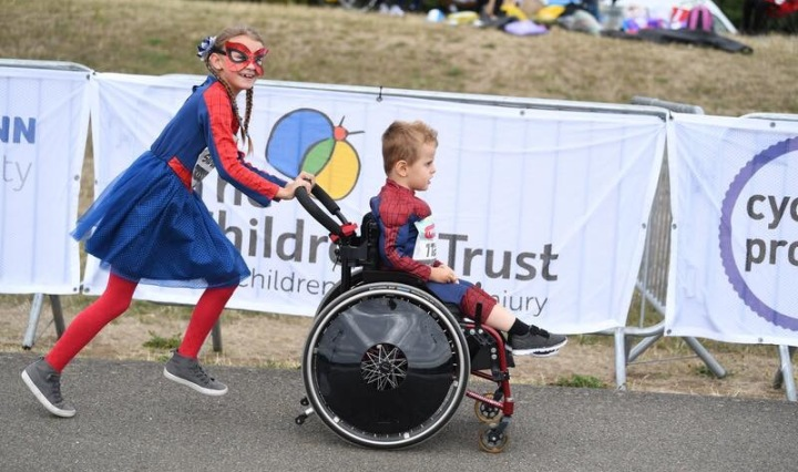 9 year old girl pushing her 5 year old brother in his wheelchair past the finish line, both dressed as superheroes