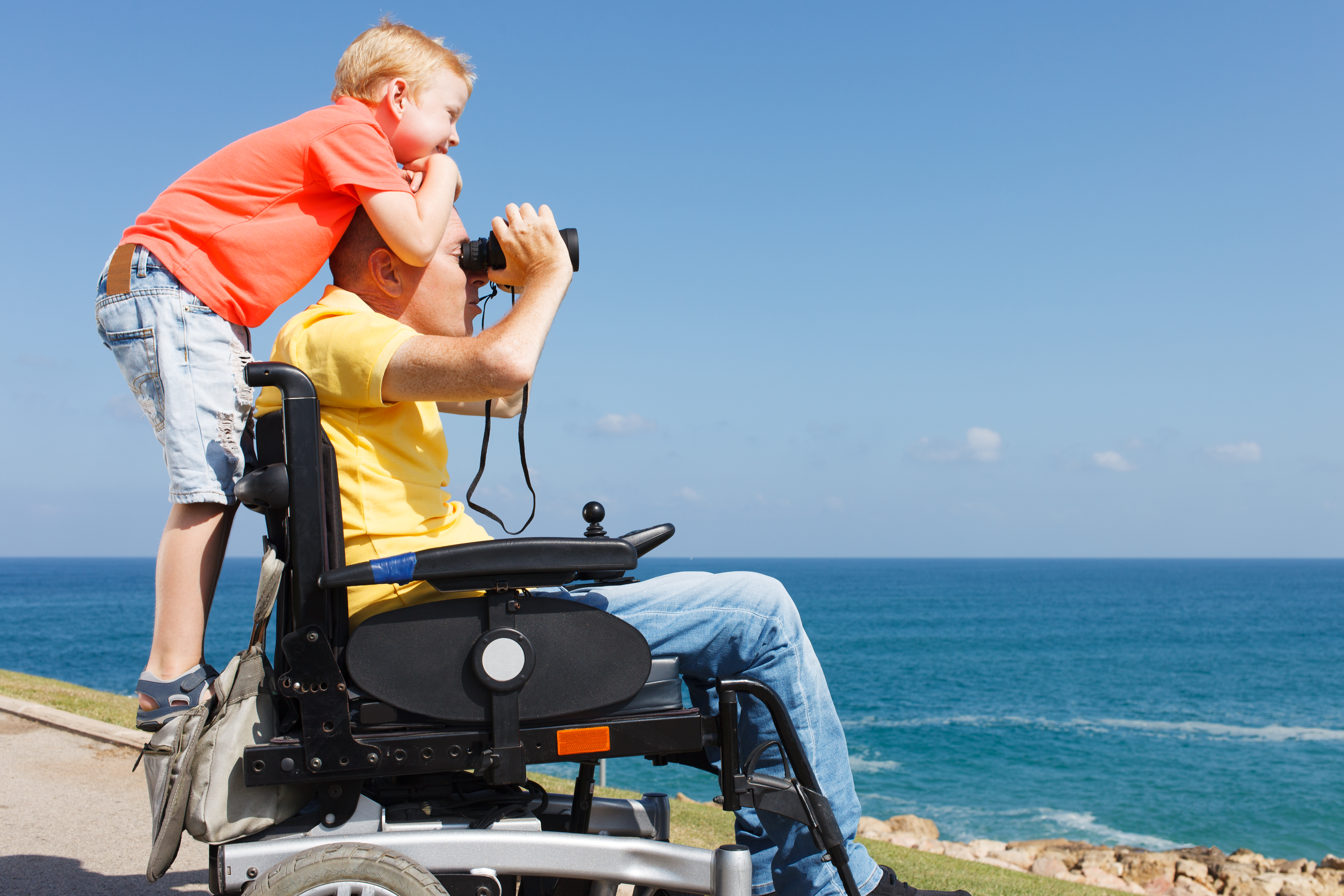 Disabled father, sat in powered wheelchair looking out to sea with a pair of binoculars with a young boy with blonde hair standing on the back of his wheelchair smiling