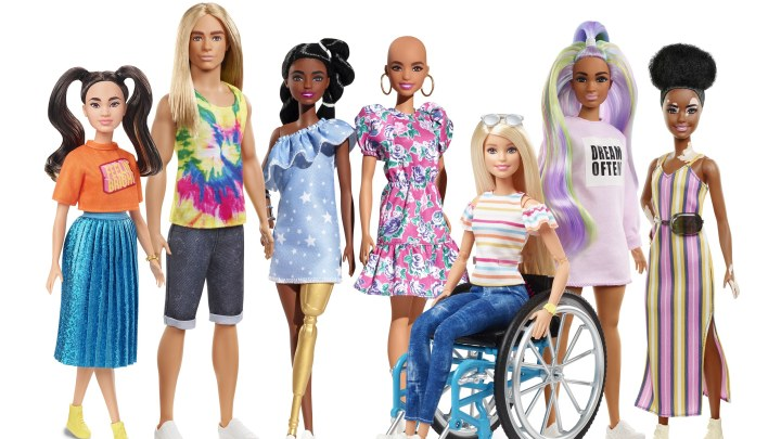 Barbie Fashionista 2020 collection featuring a barbie of chinese ethnicity, ken with long blonde hair, black barbie with prosthetic leg, white bald barbie, wheelchair user barbie, olive skinned barbie with pastel rainbow hair and makeup and a black barbie with alopecia.