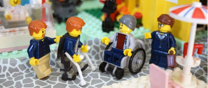 Playset of 4 legomen. The 1st legoman is wearing an exoskeleton walking device and using crutches and is supported by a helper legoman, the next is a functional wheelchair with legoman, lastly there is a character with a briefcase looking like he's about to shake the wheelchair users hand.