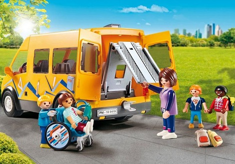 Playset of a yellow school bus with fold out tail ramp and a family ready to wheel a little boy figure in his wheelchair up into the vehicle.