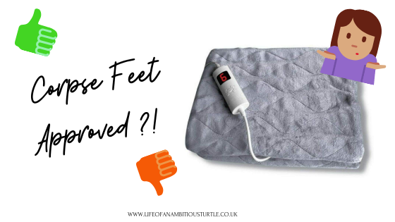 "Photo of a neatly folded grey quilted fleece electric blanket with white corded remote control with digital display. Text beside it reads ""corpse feet approved?!"" with a green thumbs up and red thumbs down"