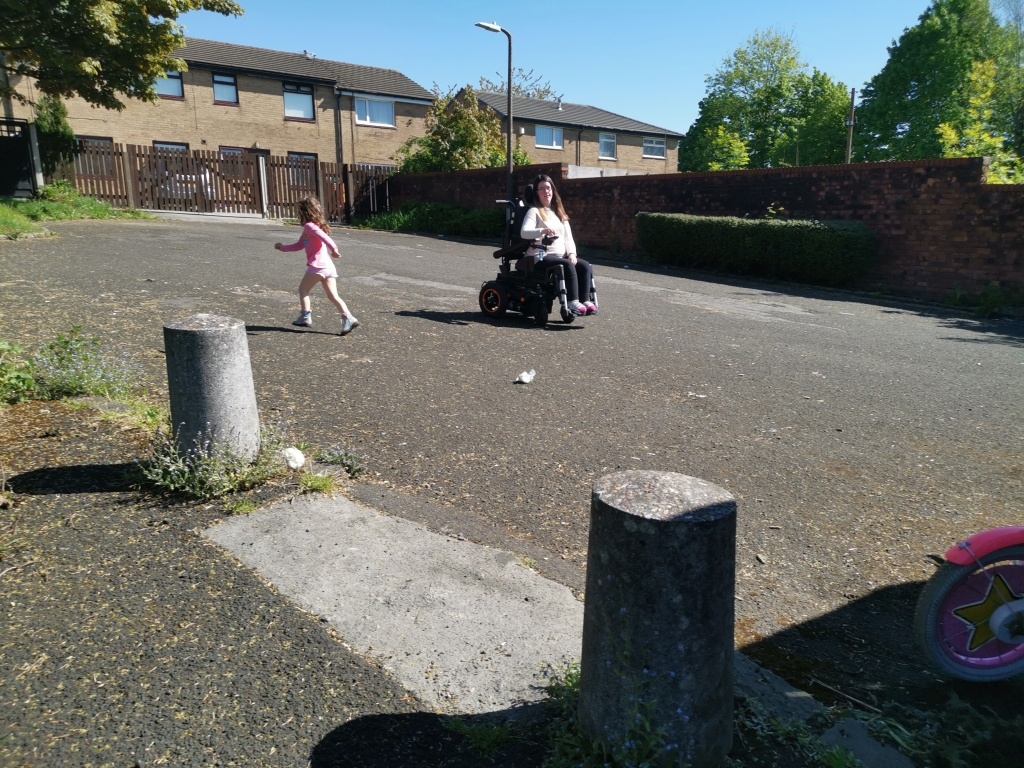 Lady with long brown hair zooming around in her black and orange accented powerchair, chasing her 4 year old daughter who is running. Both smiling and laughing.